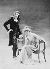 Black and white photograph with two women, one in a light dress and Victorian hairstyle seated on a bench, the other behind her in a dark pantsuit and flowing hair.