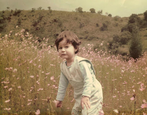 Photograph of a girl in a field of flowers. She stands slightly bent forward with her arms a little open and looks at the camera with a fearful stare.