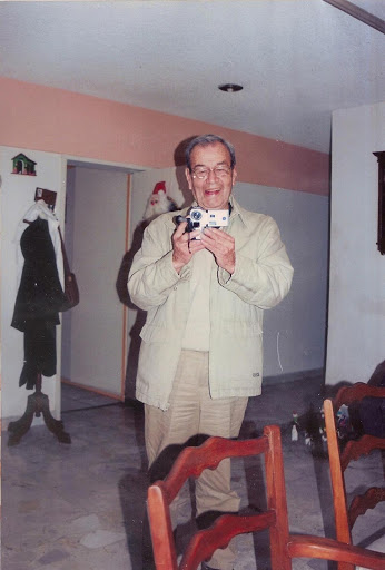 Color photograph of my grandfather standing inside a house. He is holding a video camera pointed at the photographer and smiling.