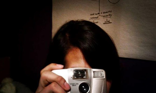 Color photograph of Ana holding a camera up to my face.