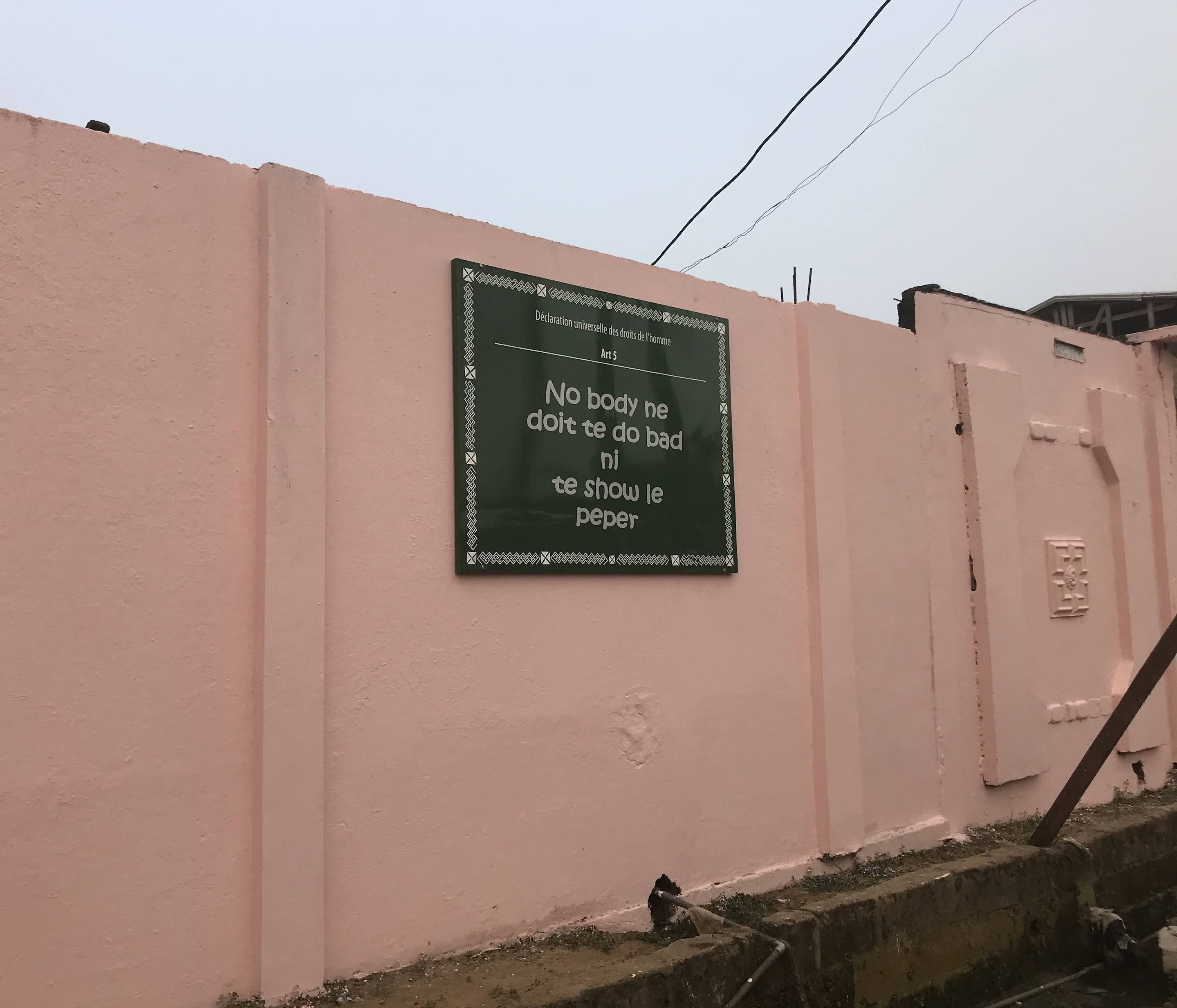 A salmon pink outdoor wall, raised upon two layers of dark bricks, featuring a black and white sign with French words.